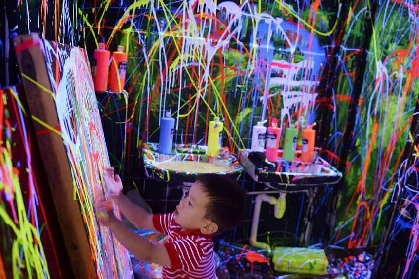 Five-year-old James Friedman uses his hands to paint with luminous paint in a toilet at The Mill which was converted into a temporary art space during The Mill x WeJungle: Destruction & Rebirth at Jalan Kilang on on Jan 21, 2015. -- ST PHOTO: MAR