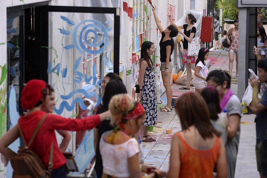 """Visitors paint the walls of The Mill during a """"colour rave"""" during The Mill x WeJungle: Destruction & Rebirth at Jalan Kilang on on Jan 21, 2015. -- ST PHOTO: MARK CHEONG"""