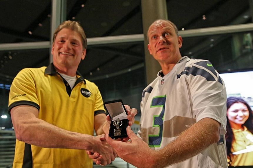 """Scoot's chief executive Campbell Wilson (right) received the """"keys"""" from Jeff Kleman, vice president Everett Delivery Centre, to the new Dreamliner from planemaker Boeing under foggy skies at its Everett factory north of Seattle. -- ST PHOTO: WANG HU"""