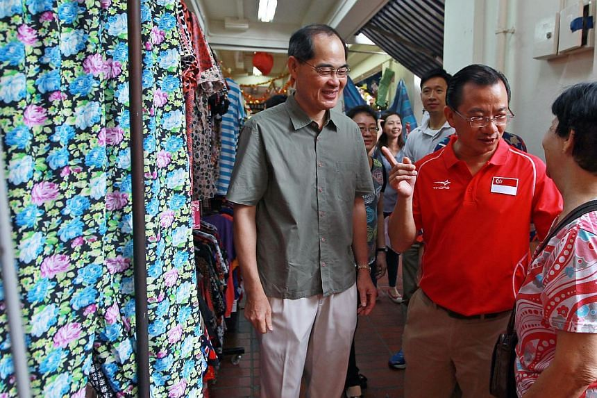 Minister for Trade and Industry Lim Hng Kiang (left) and Marine Parade GRC MP Seah Kian Peng (in red) speaking to a resident during a visit to Braddell Heights on Feb 1, 2015. -- PHOTO: LIANHE ZAOBAO