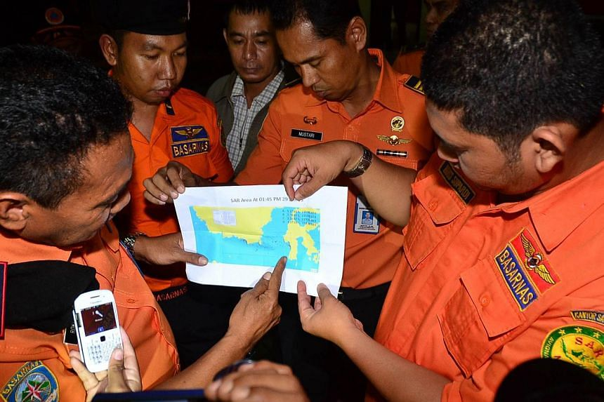 Members of an Indonesian rescue team point a finger at the of a location where they found a victim and debris of the AirAsia flight QZ8501 accident, in Makassar, South Sulawesi, on 30 Jan, 2015. -- PHOTO: AFP