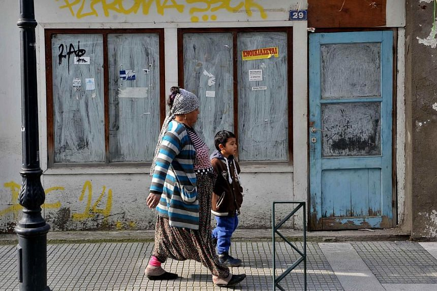 People walk past a closed shop in Komotini, northern Greece, on Jan 15, 2015.A top European Central Bank official said Saturday the institution cannot keep lending money to Greece unless the heavily indebted nation extends its bailout programme
