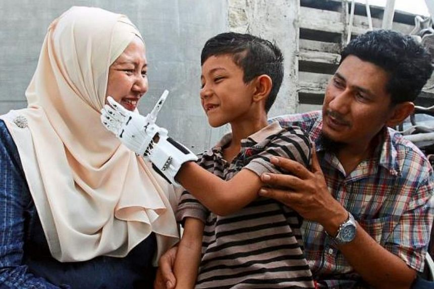 Muhammad Muqri touching his mother Nor Julaina Md Sani, 40, on the cheek with his new mechanical fingers. With them is his father Rhemi. -- PHOTO: THE STAR/ASIA NEWS NETWORK