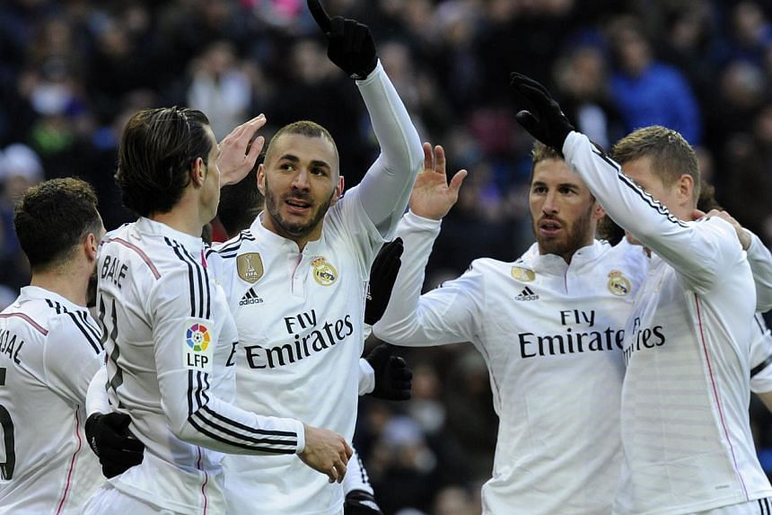 Real Madrid's French forward Karim Benzema (third left) celebrates with teammates after scoring during the Spanish league football match Real Madrid versus Real Sociedad de Futbol in Madrid on Jan 31, 2015. -- PHOTO: AFP