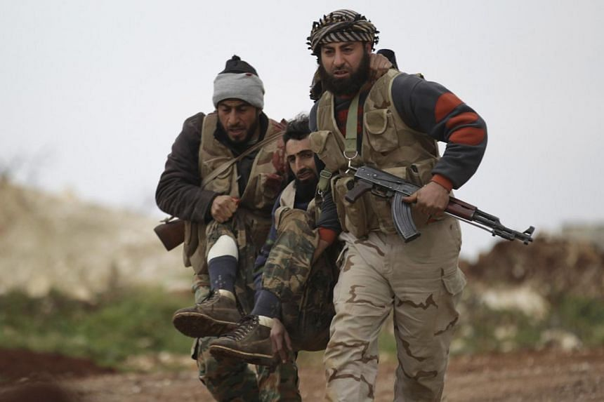 Fighters from Suqour al-Sham Brigade, which is part of the Free Syrian Army, carry a wounded member of their brigade during what activists said were clashes with forces of Syria's President Assad, in al-Arbaeen mountain area of western Idlib.--