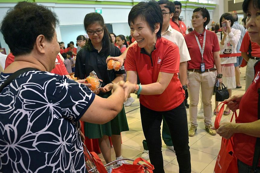 Minister in the Prime Minister's Office Grace Fu distributing goodie bags comprising two 1kg packets of rice, a packet of red dates, a packet of ginger tea and oatmeal, two mandarin oranges and ang pows to about 2,000 residents at the Yuhua Comm