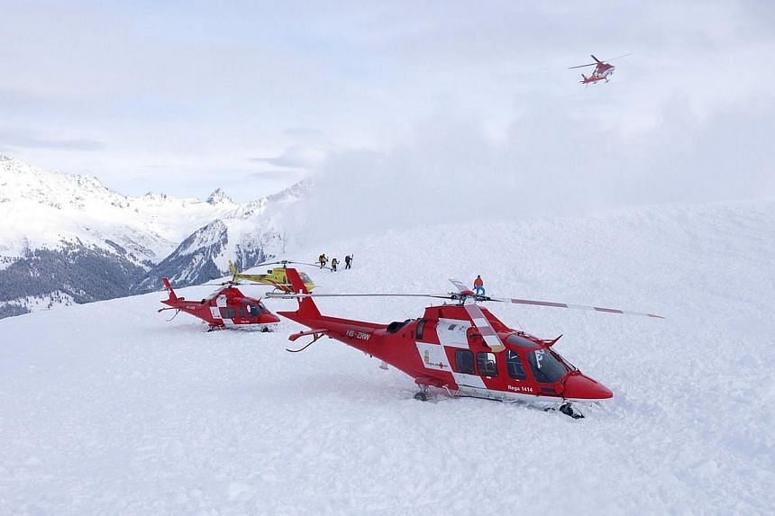 A haoudout picture taken and provided by the police of the Swiss Canton of Graubuenden on Saturday near Seewis, eastern Switzerland, shows Rescuers at the site of an avalanche that hit nine skiers on the Piz Vilan mountain at an altitude of some 2,20