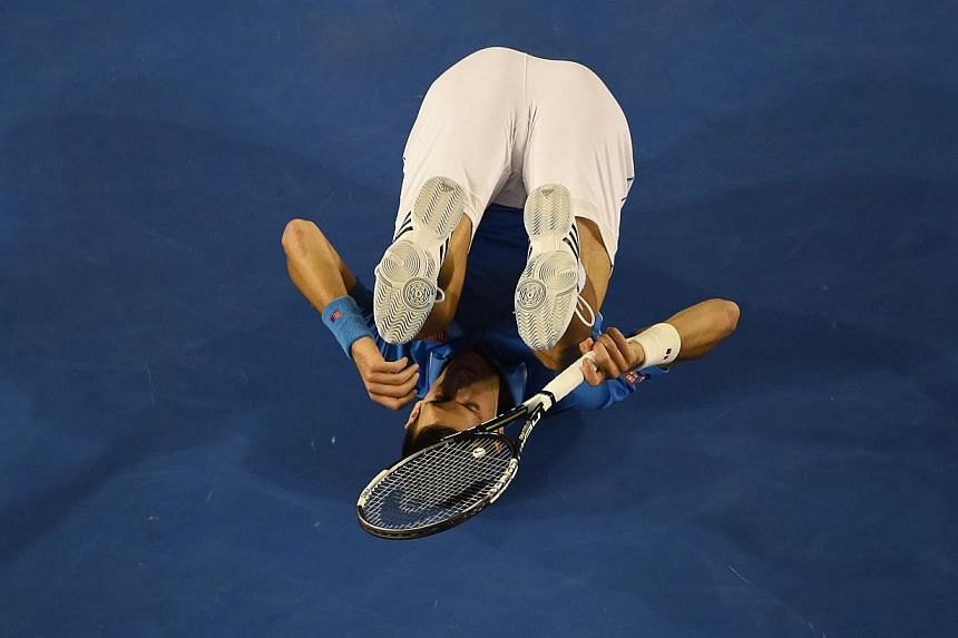 Serbia's Novak Djokovic rolls on the court during his men's singles final match against Britain's Andy Murray at the 2015 Australian Open tennis tournament in Melbourne on Sunday.-- PHOTO: AFP