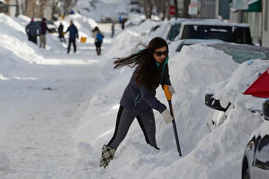 A woman digs her car out from snow in Boston, Massachusetts, USA, on Jan 28, 2015. The north-eastern United States braced for the second major snow storm in a week on Monday, Feb 2, 2015, after a huge winter system dumped more than 30cm of snow