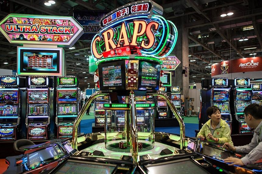 In this file picture taken on May 20, 2014, visitors try a machine at the Global Gaming Expo Asia in the world's biggest gambling hub of Macau. -- PHOTO: AFP