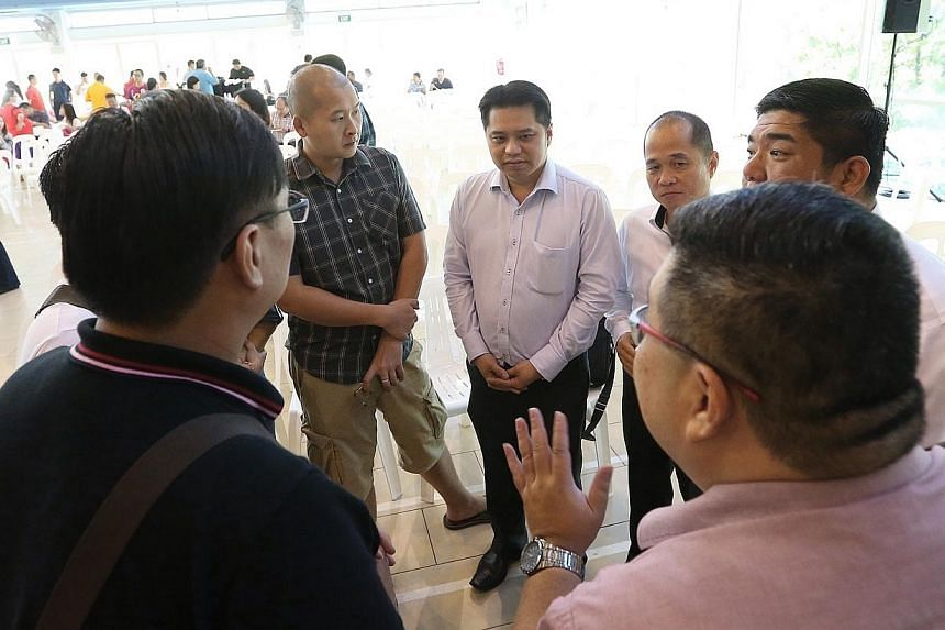 Chief executive of Life Corp Simon Hoo (centre) speaks to residents after the residents' dialogue session on Jan 4, 2015. -- ST PHOTO: NEO XIAOBIN
