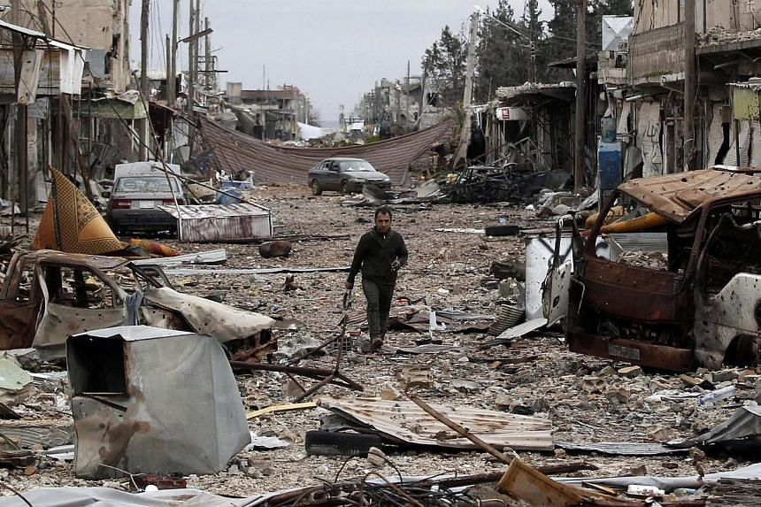 A man walks down a street filled with abandoned vehicles and debris from damaged buildings in the northern Syrian town of Kobane on Jan 30, 2015. Islamic State in Iraq and Syria (ISIS) militants are withdrawing from areas around Kobane, a group