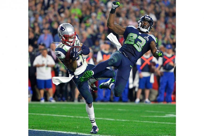 New England Patriots strong safety Malcolm Butler (left) makes an interception as he collides with Seattle Seahawks wide receiver Ricardo Lockette (right) during the final seconds of Super Bowl XLIX between the New England Patriots and the Seattle Se