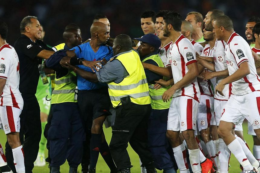 Tunisia players confront referee Seechurn Rajindraparsad (in blue) after losing their quarter-final football match of the 2015 African Cup of Nations against Equatorial Guinea in Bata onJan 31, 2015. Tunisia are facing heavy punishment after th
