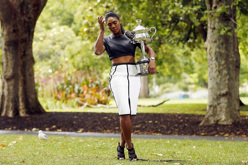 Serena Williams of the US poses with the Daphne Akhurst Memorial Cup after winning the women's singles final match at the 2015 Australian Open tennis tournament during a photo call at Melbourne's Royal Exhibition Building on Feb 1, 2015.Trees i