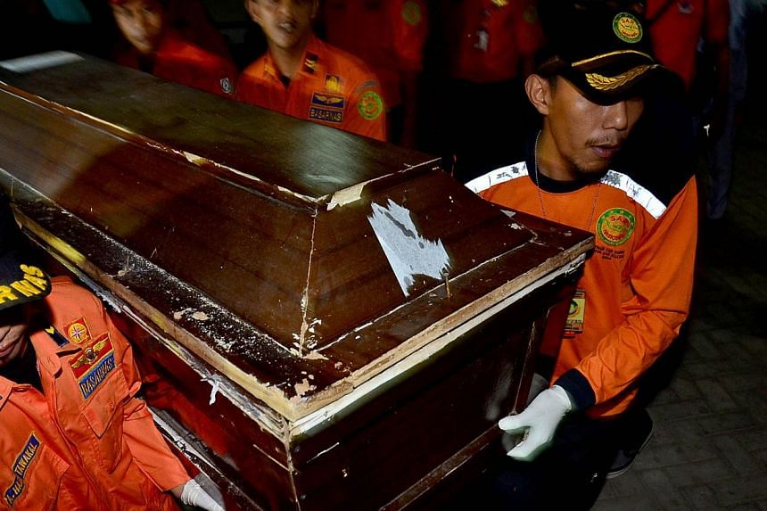 Members of an Indonesian rescue team carry a coffin with the remains of a victim of the AirAsia flight QZ8501 accident, in Makassar, South Sulawesi on Jan 30, 2014. The AirAsia flight QZ8501's emergency locator transmitter (ELT) has reportedly been f