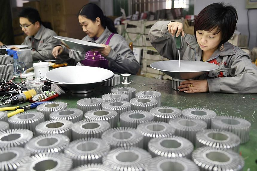 Workers assemble LED lights at a factory in Zouping, in eastern China's Shandong province. The risk of global deflation looms large for 2015 as surveys of China's mammoth manufacturing sector showed excess supply and deficient demand in January drove
