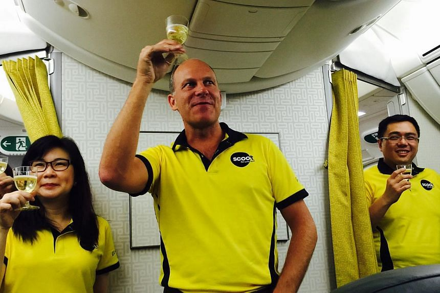 Scoot chief executive officer Campbell Wilson (centre) making a mid-air toast on board the budget airline's first Boeing 787 during the delivery flight from Seattle to Singapore. -- ST PHOTO: JERMYN CHOW