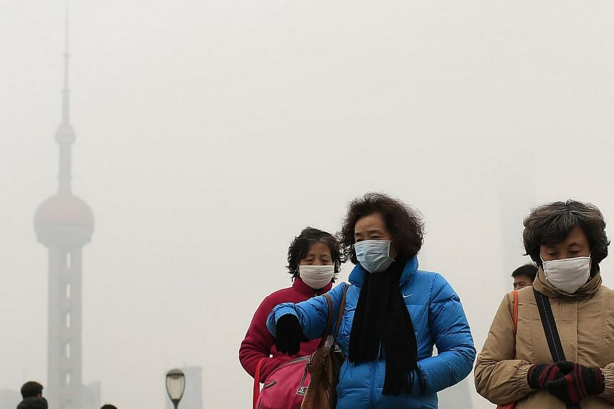 Woman wearing face masks on the Bund in front of the Oriental Pearl TV Tower during a hazy day in downtown Shanghai on Jan 26, 2015. -- PHOTO: REUTERS