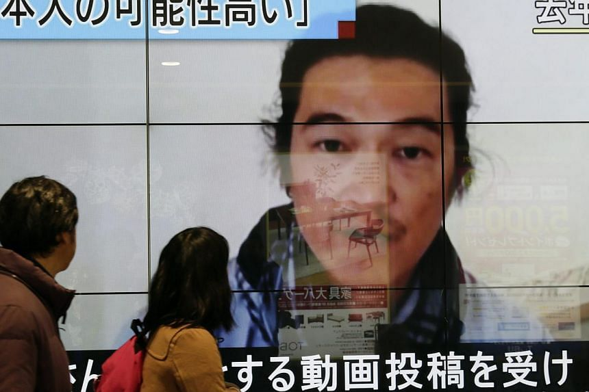Passersby watching an image of Kenji Goto pictured on last October with news reporting the Japanese hostage was killed by an Islamic State militant. The United Nations Security Council demanded the immediate release of all hostages held by the Islami