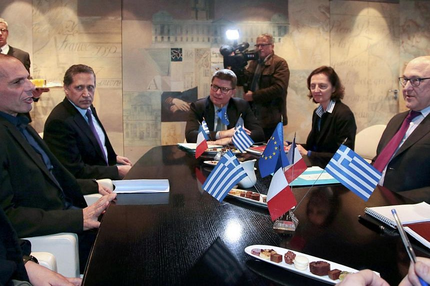 French Finance Minister Michel Sapin (right) and Greek Finance Minister Yanis Varoufakis (left) attend a meeting at the Bercy Finance Ministry in Paris on Feb 1, 2015. Greece's leftist government began its drive to persuade a sceptical Europe to acce