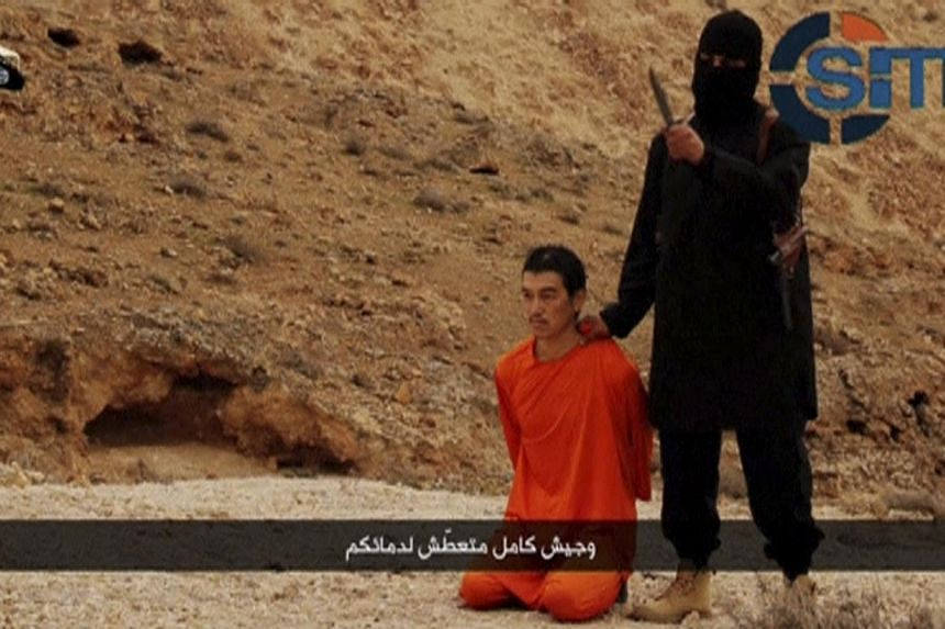 An Islamic State fighter stands next to a man kneeling on the ground purported to be Japanese journalist Kenji Goto in an unknown location in this still image from a video released by Islamic State on Jan 31, 2015. -- PHOTO: REUTERS