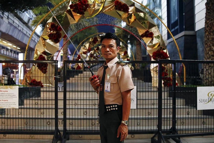 A guard secures the area around Siam Paragon mall in central Bangkok early this morning. Two pipe bombs exploded outside the luxury shopping mall in Bangkok on Sunday in an attack which Thai police said was aimed at raising tension in a city living u