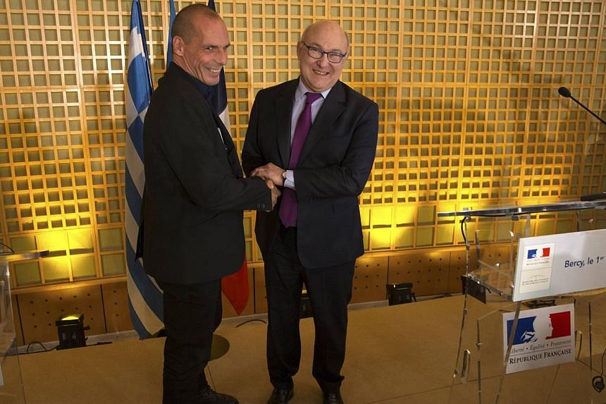 French Finance Minister Michel Sapin (right) and Greek Finance Minister Yanis Varoufakis arrive at a joint news conference after a meeting at the Bercy Finance Ministry in Paris on Sunday. -- PHOTO:REUTERS