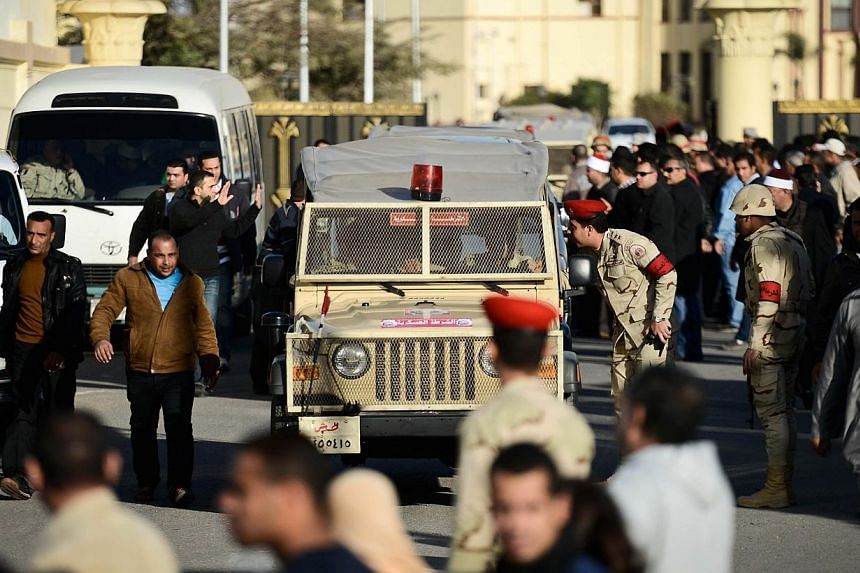 Egyptian members of the armed forces patrol outside al-Maza military airport where the bodies of the members of security forces who were killed in North Sinai province had been flown on Jan 30, 2015 in the capital Cairo.Cairo airport officials