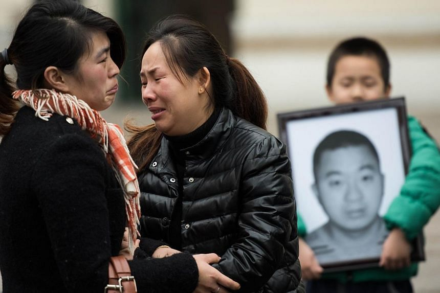 Ms Fan Ping (centre), wife of Du Shuanghua, who died in a stampede on New Year's Eve, cries after the funeral ceremony of her husband, next to her son who is holding a portrait, in Shanghai on Feb 3, 2015. Du's funeral was held on Tuesday, after