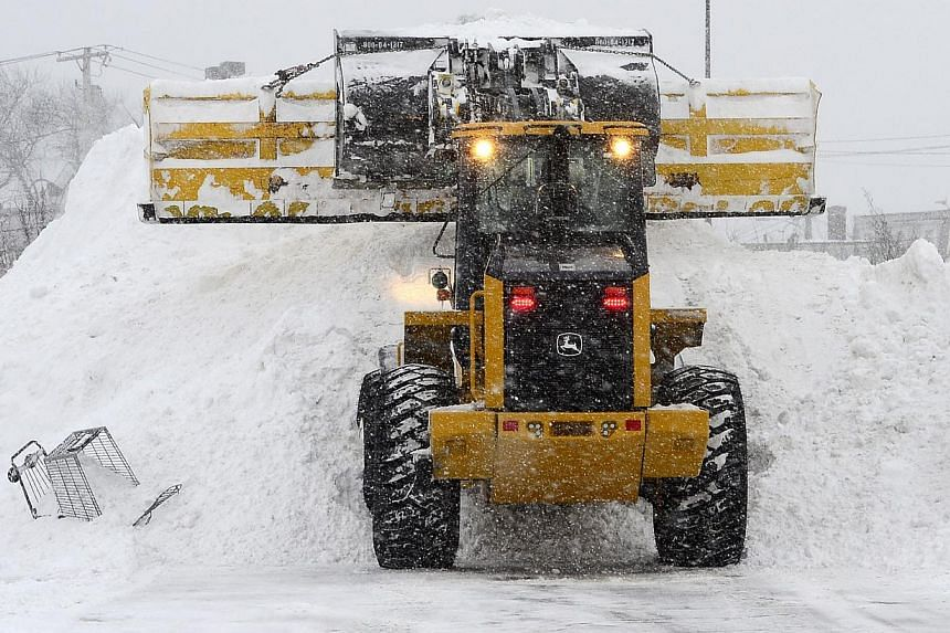 A loader piling snow in the parking lot of the South Bay shopping plaza in Boston, Massachusetts on Feb 2, 2015. -- PHOTO: EPA