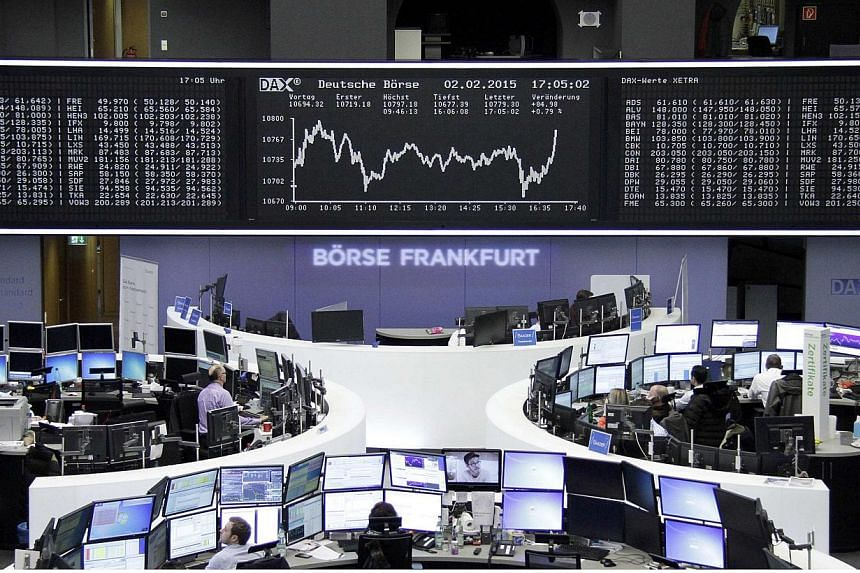 Traders work at their screens in front of the German share price index DAX board at the stock exchange in Frankfurt on Feb 2, 2015.European stocks rose early on Tuesday, Feb 3, lifted by hopes for an agreement on the Greek debt stand-off after