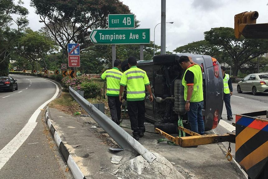 The car lying on one side on the PIE road divider near Tampines Ave 5 exit.-- ST PHOTO:TIFFANY GOH