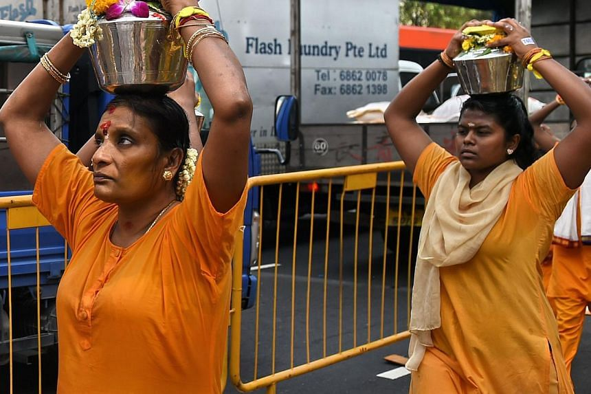 Hindu devotees carrying offerings of milk along a procession route in Singapore's Little India district as part of the annual Thaipusam festival on Feb 3, 2015. -- PHOTO: AFP