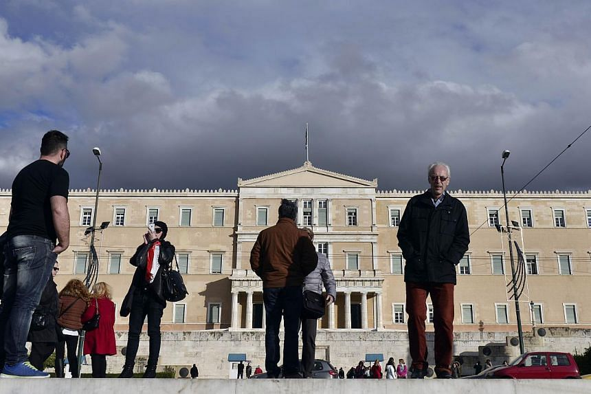 "People stand in front of the Greek parliament in Athens on Feb 2, 2015. ""Grexit"" - a Greek exit from the euro zone - is a catastrophe that can be avoided. -- PHOTO: AFP"