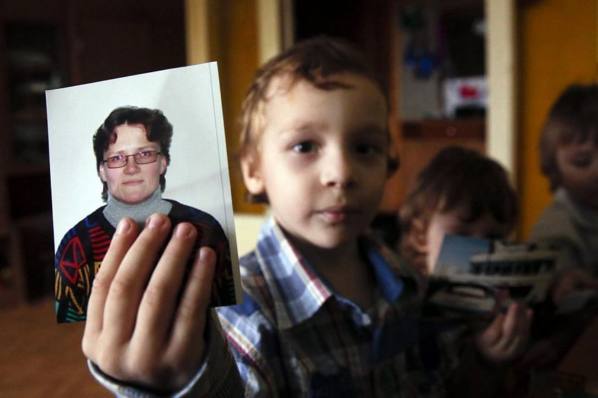 Artur, son of Russian activist Svetlana Davydova and her husband Anatoly Gorlov, holds up a photo of his mother to the camera, at their home in Vyazma, nine months after she was arrested on suspicion of treason. -- PHOTO: REUTERS
