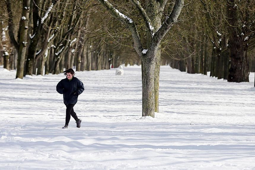 A woman jogs across snow covered la Quinta Park after a heavy snowfall in Burgos, Spain on Sunday. -- PHOTO: AFP