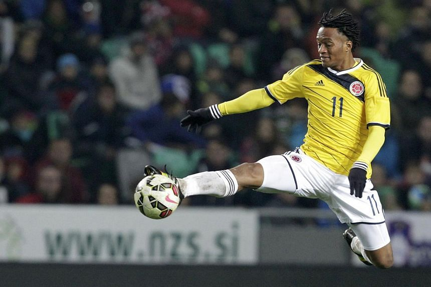 Colombia's Juan Cuadrado jumps to reach the ball during their international friendly soccer match against Slovenia in Ljubljana in November last year. -- PHOTO: REUTERS