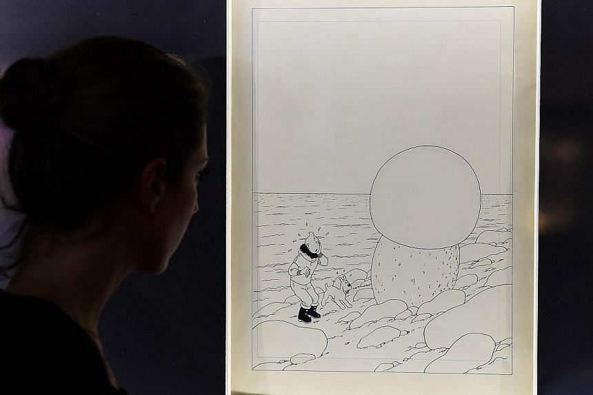 A woman looks at the original artwork to the cover of Tintin et L'etoile Mysterieuse (Tintin And The Shooting Star) by late Belgian cartoonist Herge at the Brussels Antiques and Fine Art Fair, in Brussels. -- PHOTO: AFP
