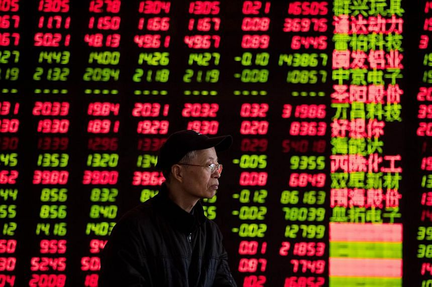 An investor looks at stock informations at a trading hall of a securities firm in Shanghai on Jan 28, 2015. China's stocks rebounded from the longest losing streak since October after benchmark money-market rates dropped and speculation grew that the