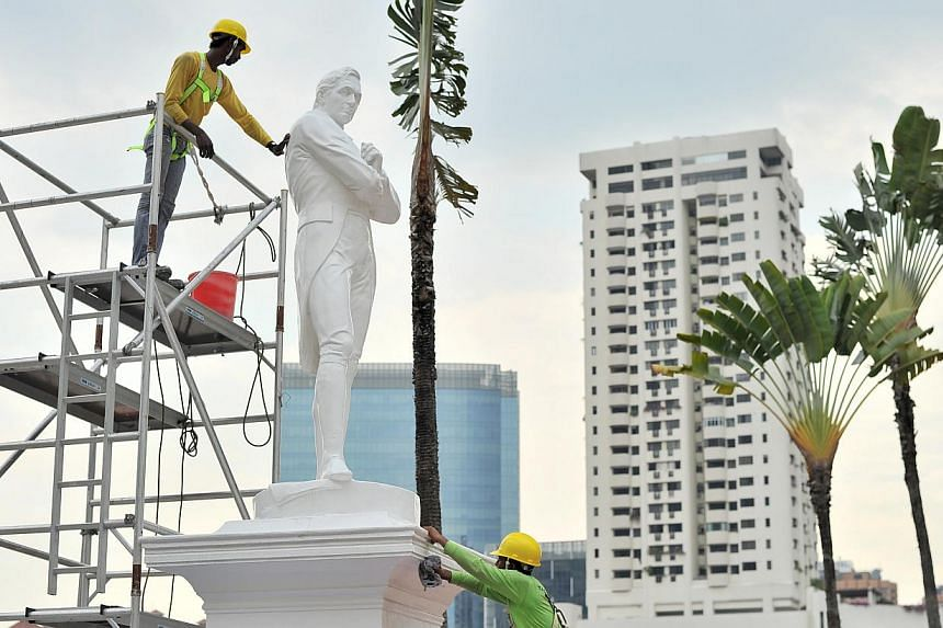 The statue of Sir Stamford Raffles being cleaned in 2014. -- PHOTO: ST FILE