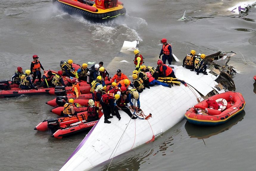 Search and rescue team members operate on a TransAsia Airways passenger plane which crashed into the Keelung River in Taipei, Taiwan on Feb 4, 2015, shortly after taking off from the Taipei Songshan Airport for Kinmen Island. -- PHOTO: EPA