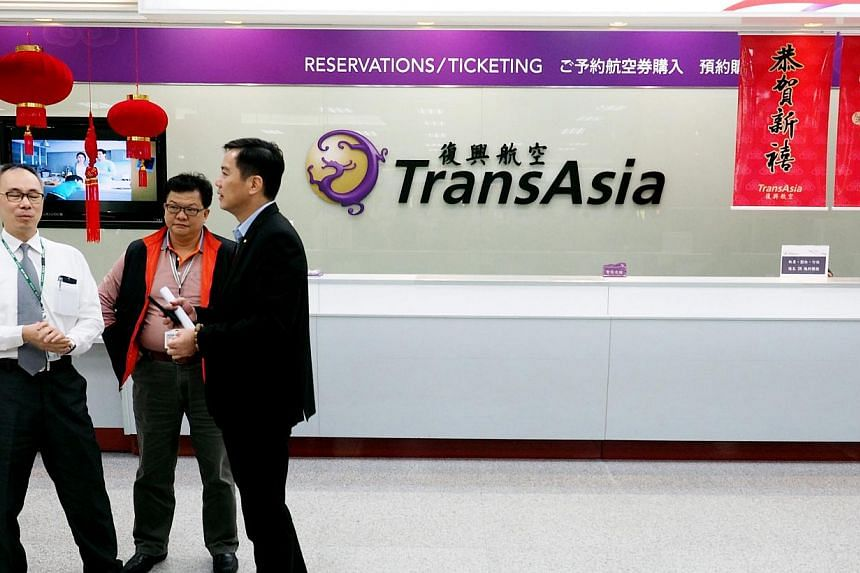 Unidentified people stand in front of the counter of TransAsia Airways at the Taipei Songshan Airport in Taipei, Taiwan, on Feb 04, 2015. Relativesof some passengers on board the TransAsia Airways plane that crashed in Taipei on Wednesday have