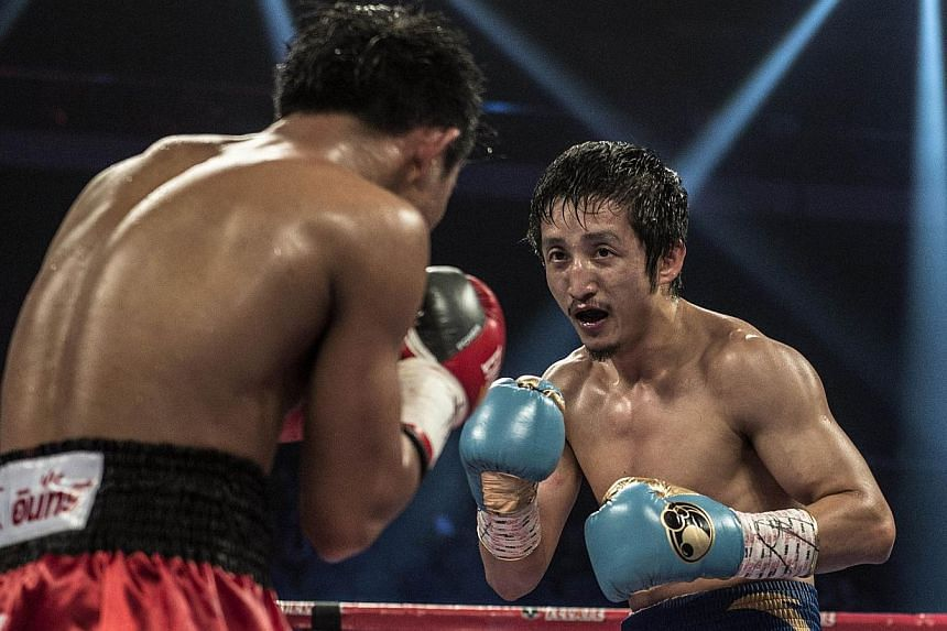 Zou Shiming (right) of China competes against Yokthong Kokietgym of Thailand in their flyweight bout in Macau on Fe 22, 2014.Double Olympic champion Zou has vowed to put China on the global boxing map by winning his first professional world tit