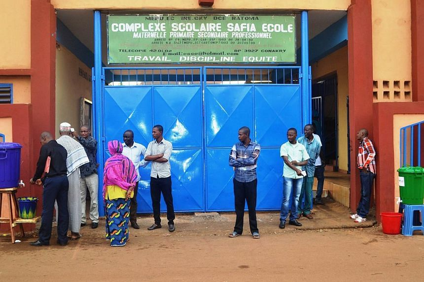 People stand outside the Safia in Conakry on Jan 19, 2015as students head back to school after nearly four months of school recess due to the Ebola outbreak. Sierra Leone said on Wednesday it would reopen the country's schools on March 30, afte