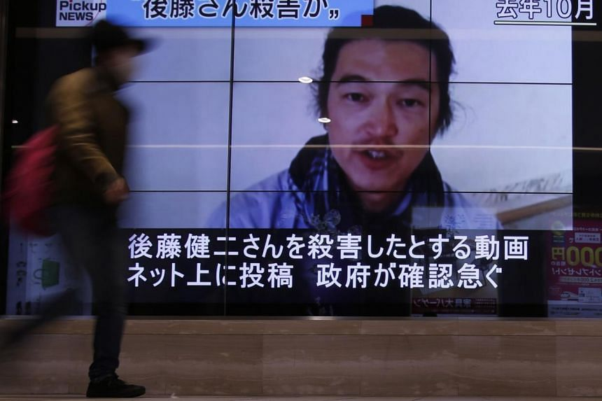 A pedestrian walks past television screens displaying a news program about Japanese journalist Kenji Goto, who was held hostage by Islamic State militants, on a street in Tokyo on Feb 1, 2015.The Islamic State in Iraq and Syria (ISIS) has commi
