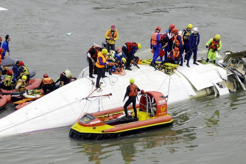 Search and rescue team members operate on a TransAsia Airways passenger plane that crashed into the Keelung River in Taipei, Taiwan, on Feb 04, 2015, shortly after taking-off from the Taipei Songshan Airport for Kinmen Island.The chief executiv