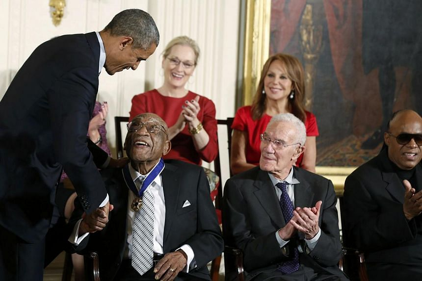 US President Barack Obama presents a Presidential Medal of Freedom to golfer Charles Sifford (front left) as fellow recipients (front row, from right) singer Stevie Wonder,economist Robert Solow, (back row, from right) actress Marlo Thomas&nbsp