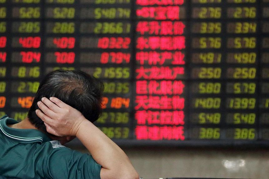 A customer looking at an electronic stock board at a securities firm in Shanghai, China, on July 1, 2013. -- PHOTO: BLOOMBERG