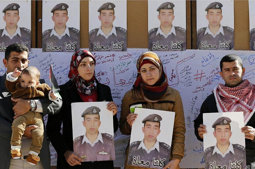 Relatives of Islamic State captive Jordanian pilot Muath al-Kasaesbeh hold pictures of him as they join students during a rally calling for his release, at Jordan University in Amman Feb 3, 2015. -- PHOTO:REUTERS